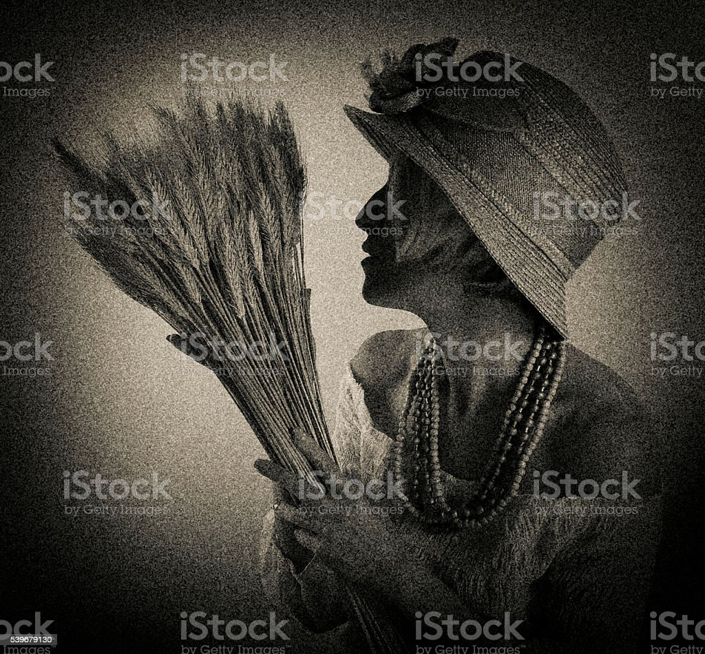 Antique photo of a woman gardener holding bundle of wheat stock photo