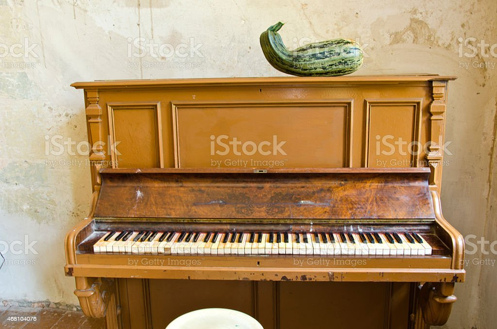 antique piano and green zucchini courgette in old manor room stock photo