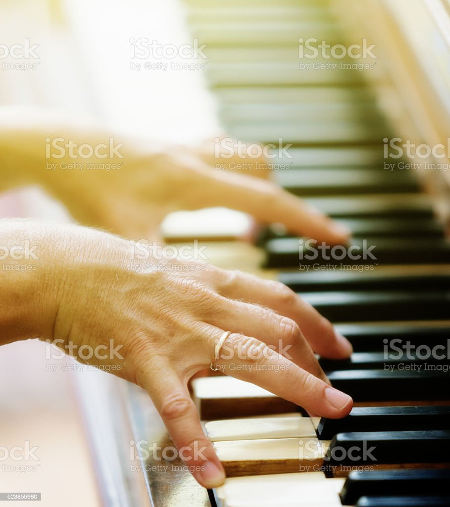 Antique piano played by woman in warm sunlight stock photo