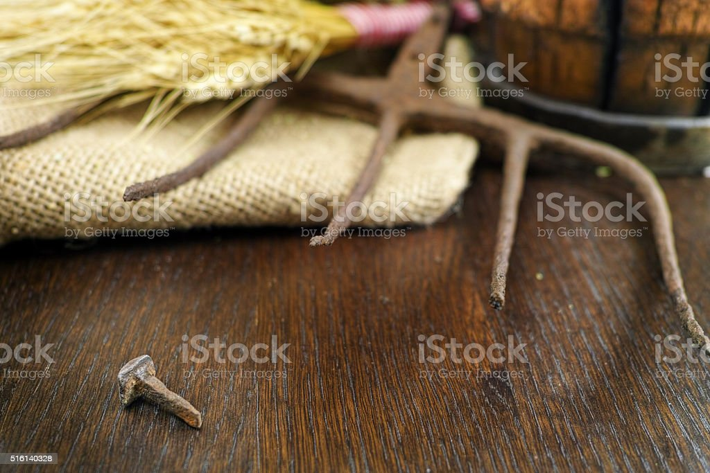 Antique pitchfork and forget iron nail on burlap closeup stock photo