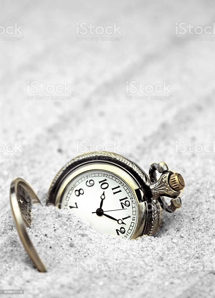 Antique pocket watch buried in sand stock photo
