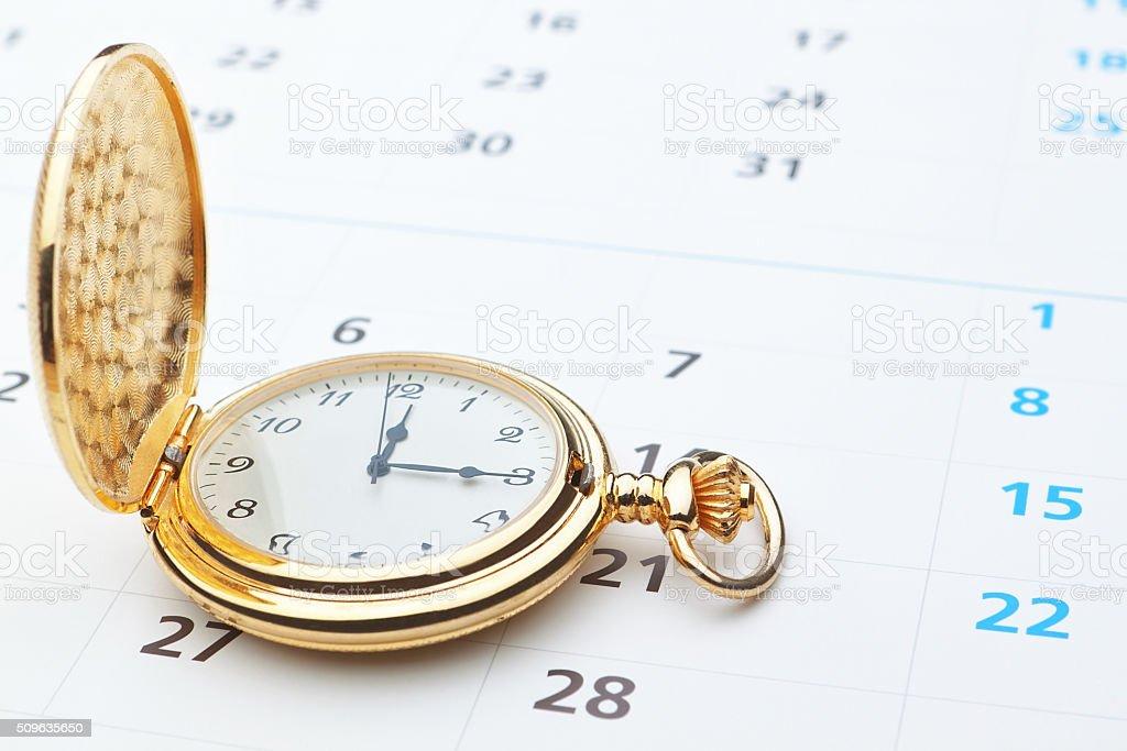 Antique pocket watch on a calendar. stock photo