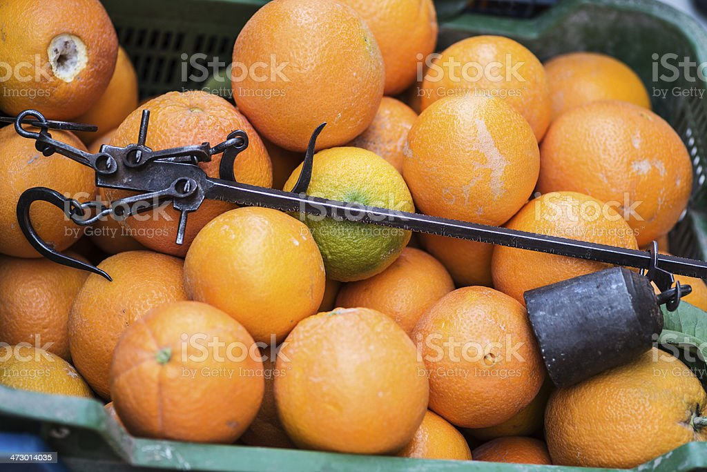 Antique Roman steelyard in a box with oranges royalty-free stock photo