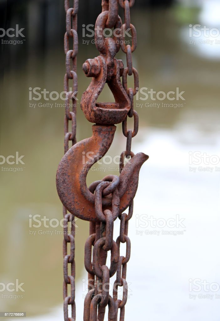 Antique rust of steel hook  carry steel chain and canal background. stock photo