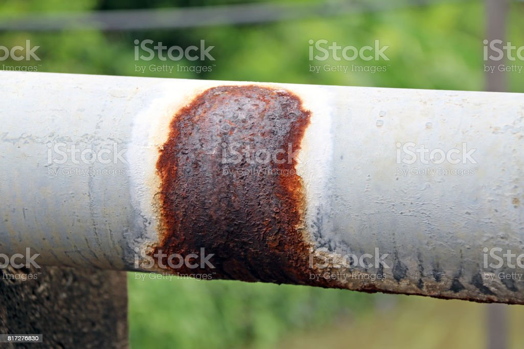 Antique rust Water pipes for village hydrant water on green background. stock photo