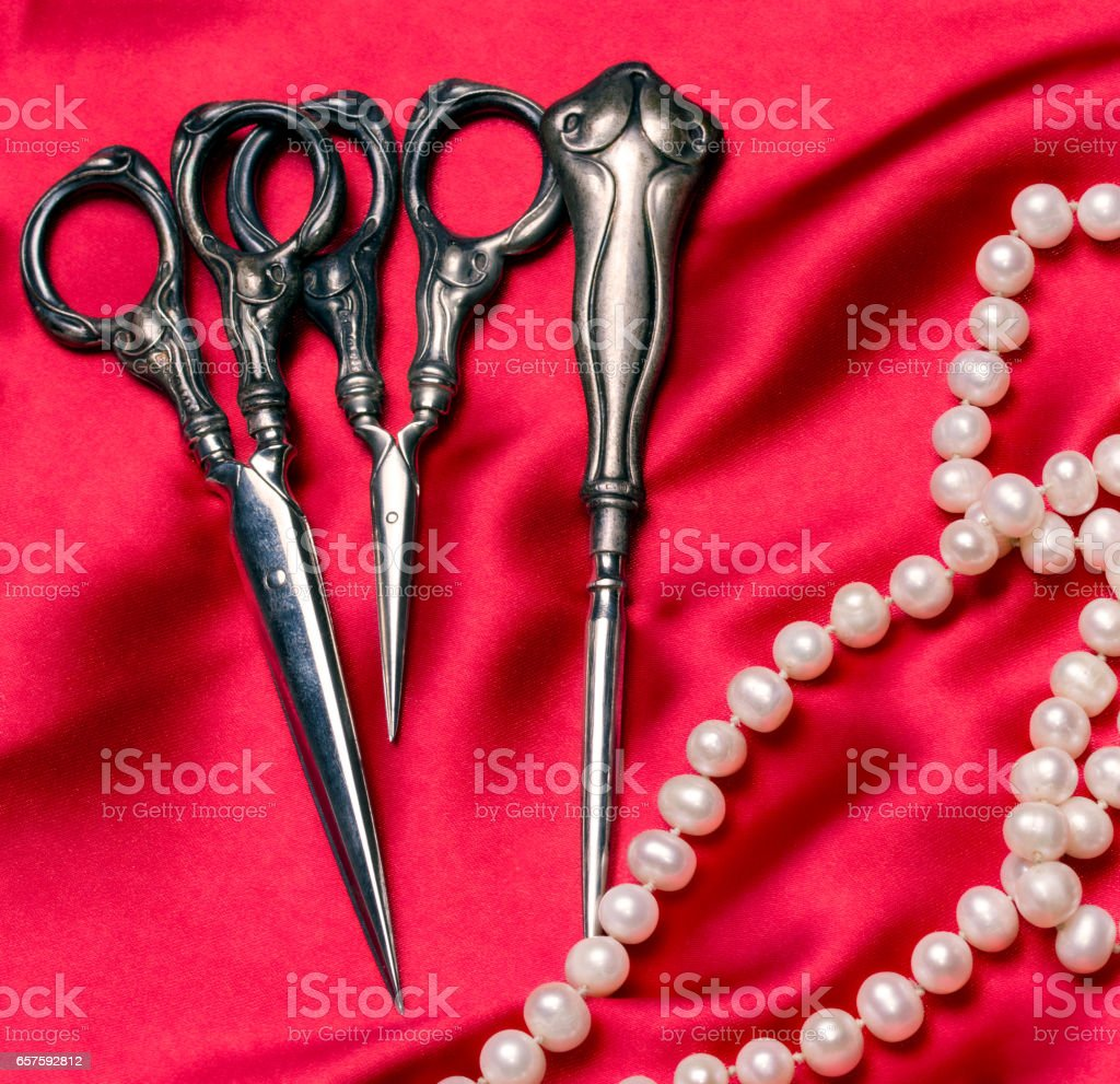 Antique sewing tools and a pearl necklace on a red silk stock photo