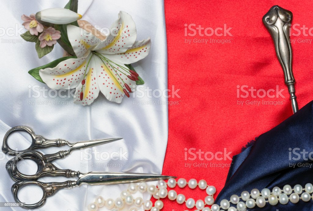 Antique sewing tools, porcelain lily and a pearl necklace on a silk cloth stock photo