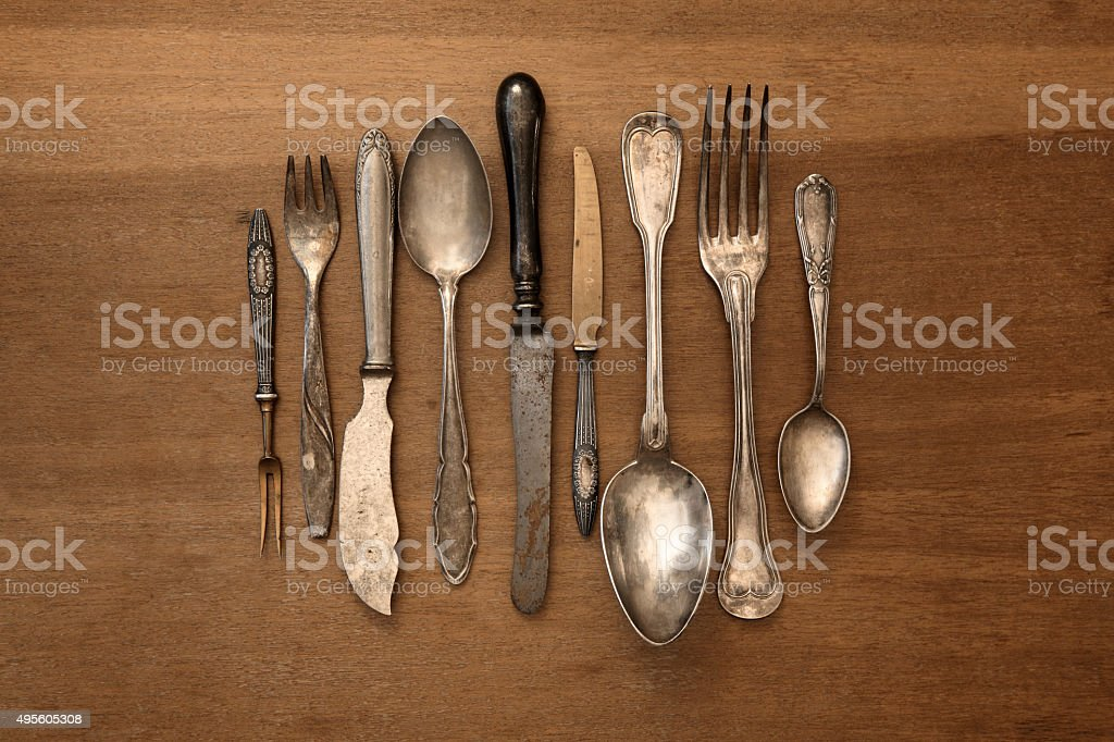 Antique silverware arranged on a wooden table stock photo