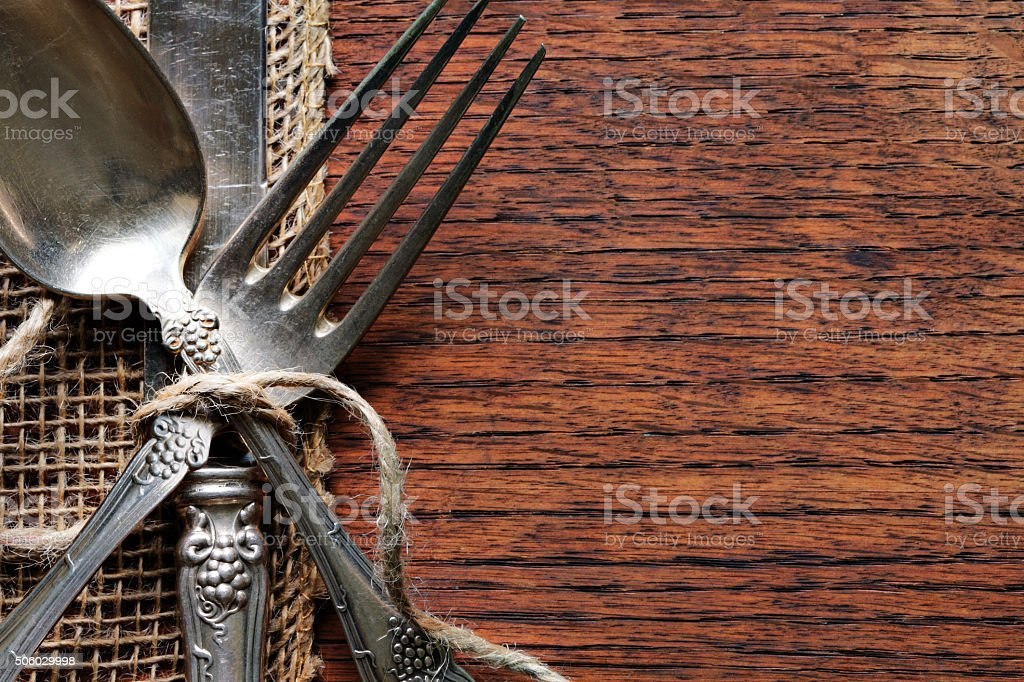 Antique Silverware On Burlap And Wood Grain Surface stock photo