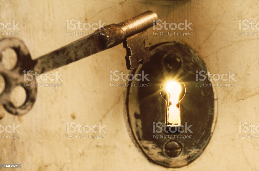 Antique Skeleton Key With Light Beams from Keyhole stock photo