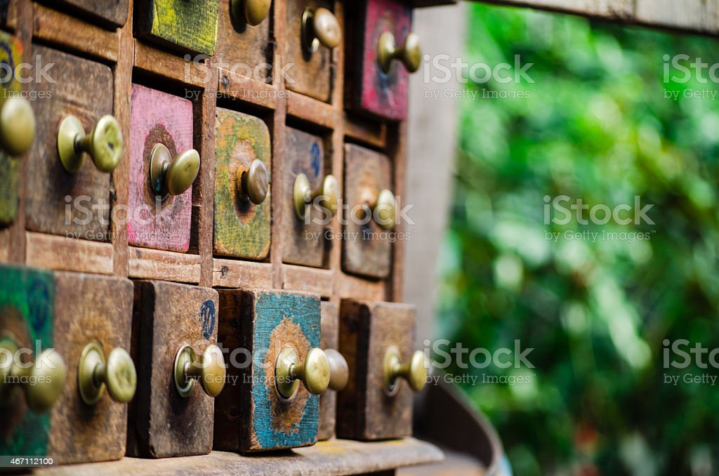 Antique Spice Drawers with Brass Handles with Green Foliage Background stock photo