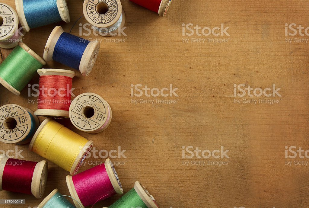 Antique spools of thread on a wooden background stock photo