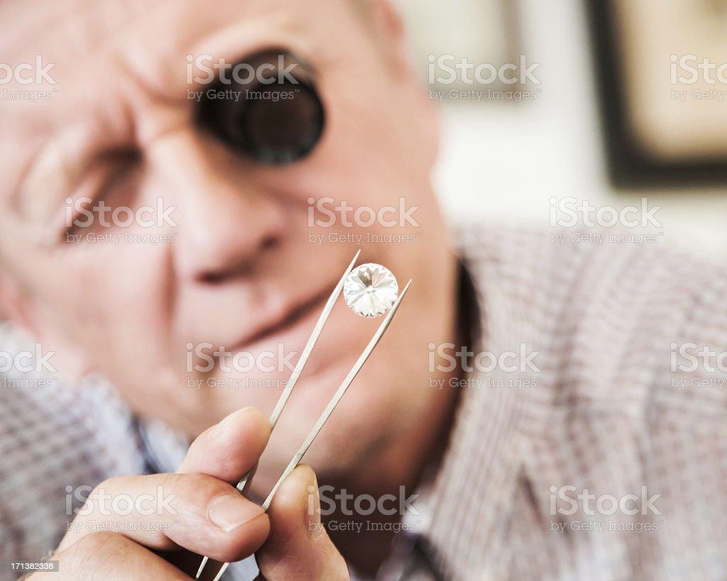 Antique Store Owner Examining Jewelery stock photo