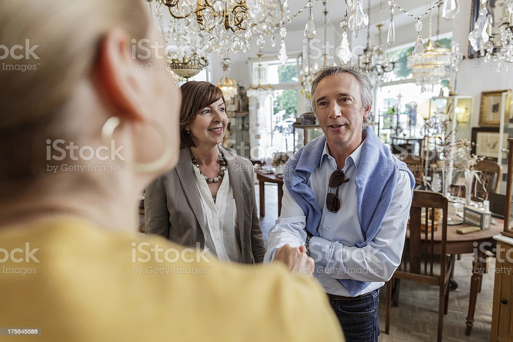 Antique store owner greeting customers stock photo