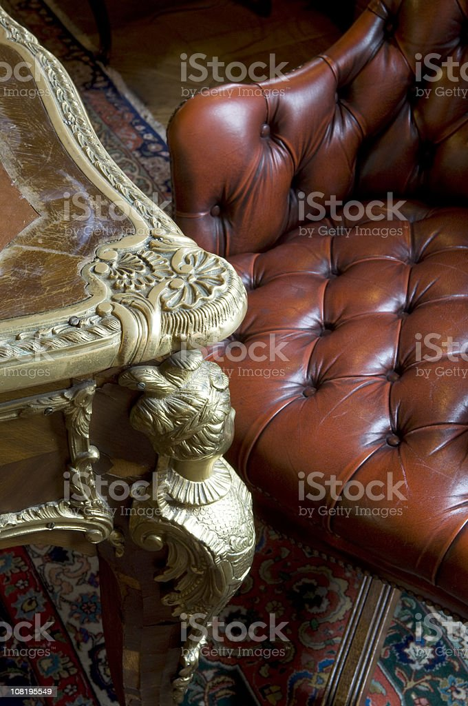 Antique Table and Chesterfield Leather Armchair with Oriental Rug stock photo