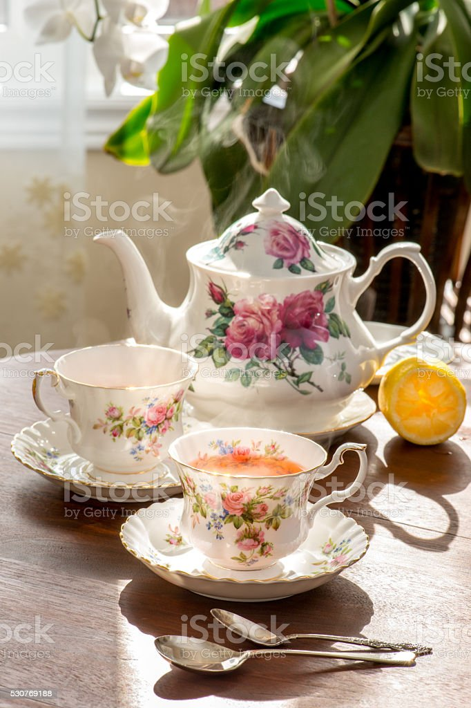 Antique tea table in warm afternoon sunlight. stock photo