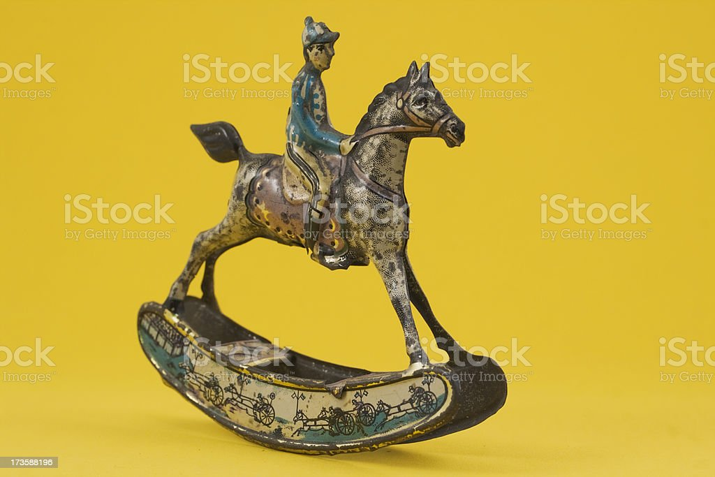 Antique tin penny toy horse with rider on yellow background. stock photo