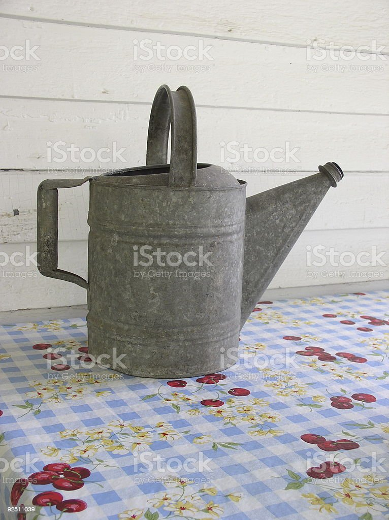 Antique Tin Watering Can on Table stock photo