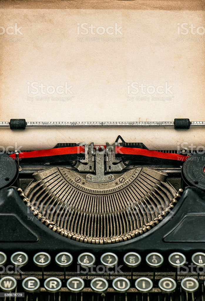 Antique typewriter with aged textured paper sheet stock photo