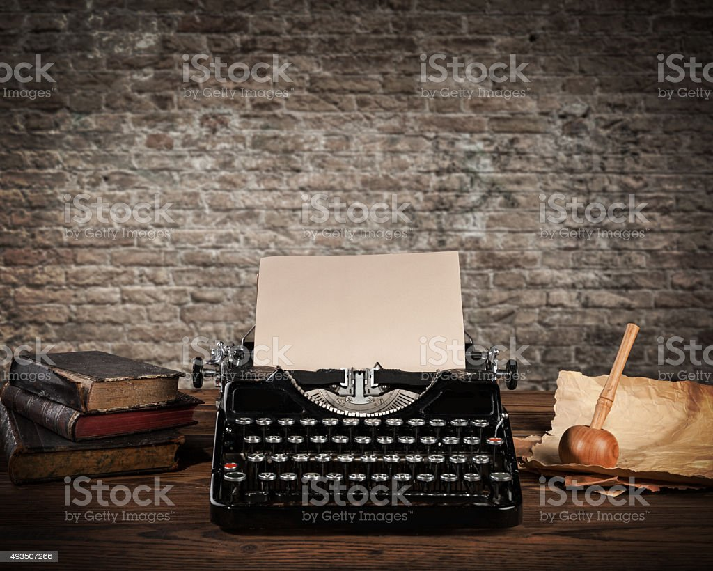 Antique typewriter with grungy brick wall stock photo