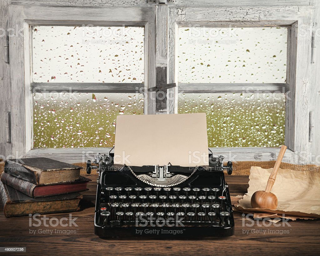 Antique typewriter with old window stock photo