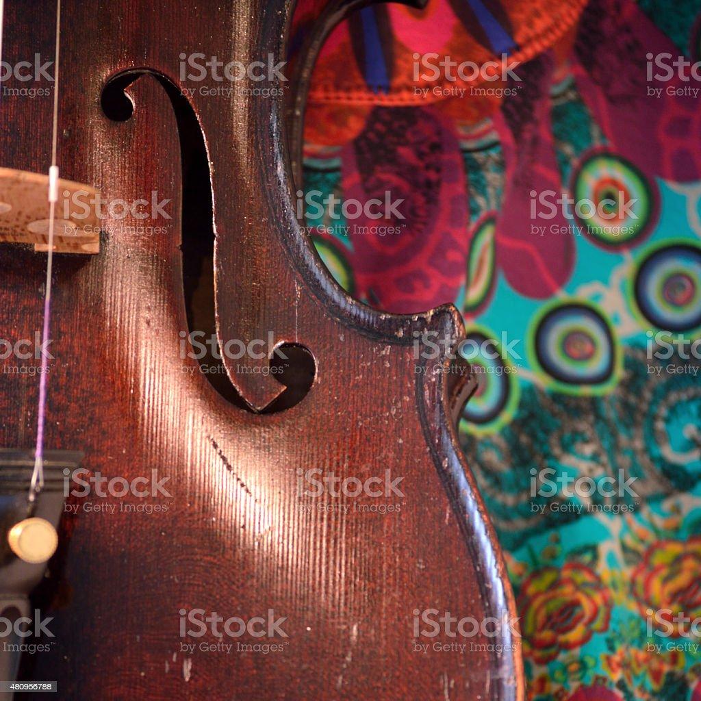 Antique violin closeup against colorful print stock photo