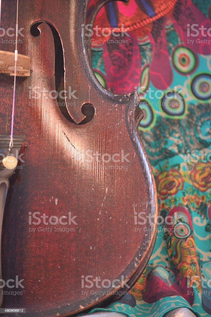 Antique violin closeup against quirky fabric print stock photo