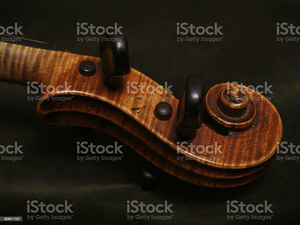 Antique Violin Scroll on Dark Green Velvet Background royalty-free stock photo