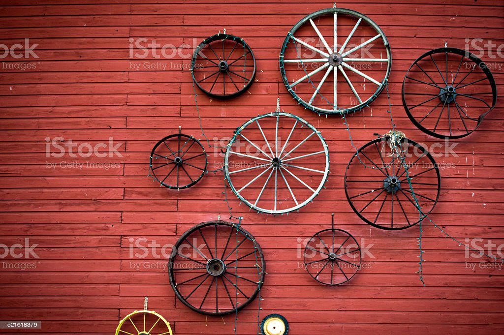 Antique wagon wheels on an old barn stock photo