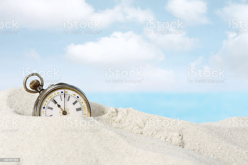 Antique watch in the sand stock photo