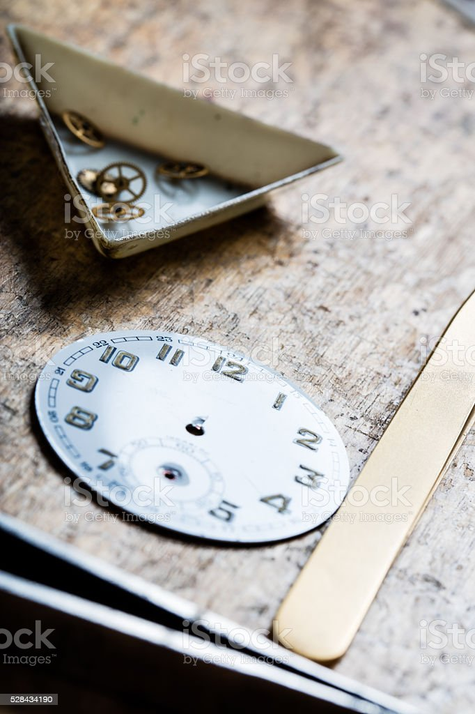 antique watch quadrant and clockworks on a repair table stock photo