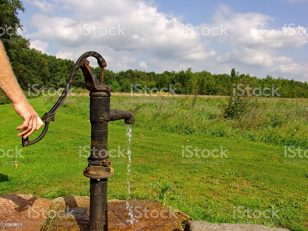 Antique well pump in a nice country setting stock photo