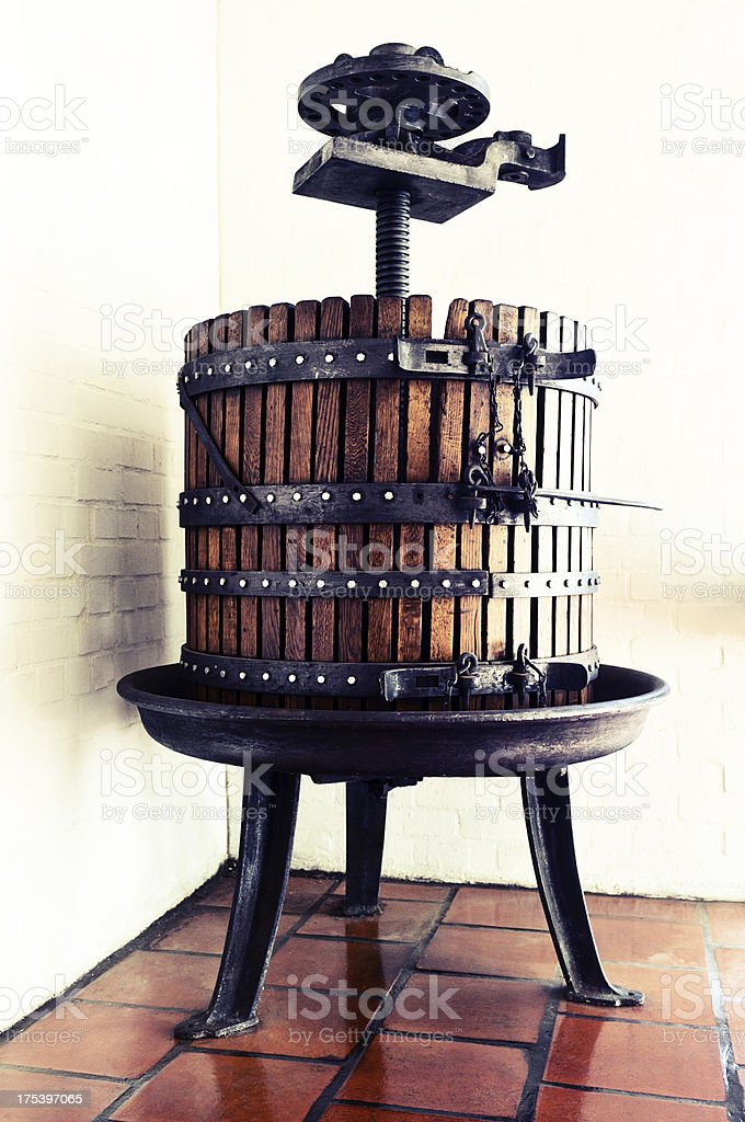 Antique wine press on quarry-tiled floor in winery cellar stock photo