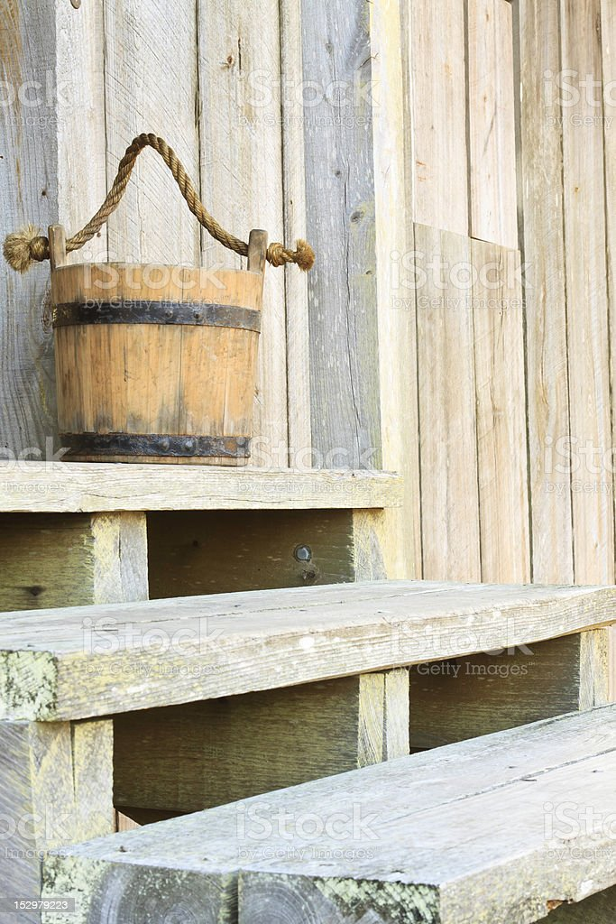 Antique Wood Bucket On Steps Of Farmhouse stock photo