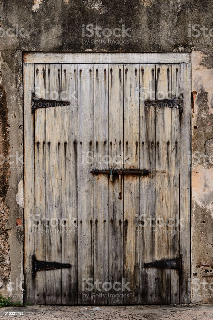 Antique wooden door on a weathered wall. stock photo