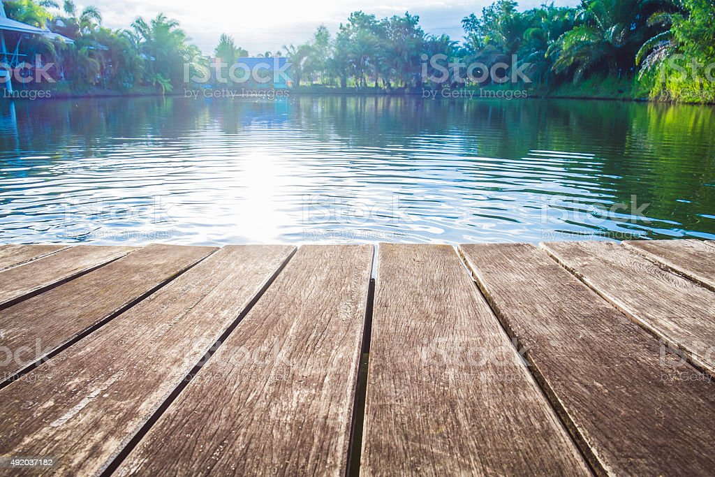 antique wooden pier on the lake with sunlight effects stock photo