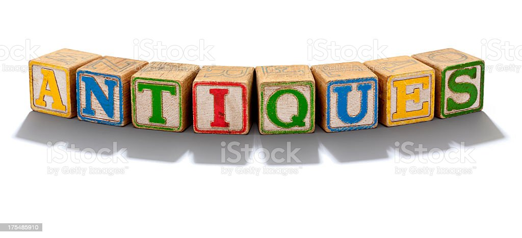 Antiques spelled out with old toy Blocks, White Background. royalty-free stock photo