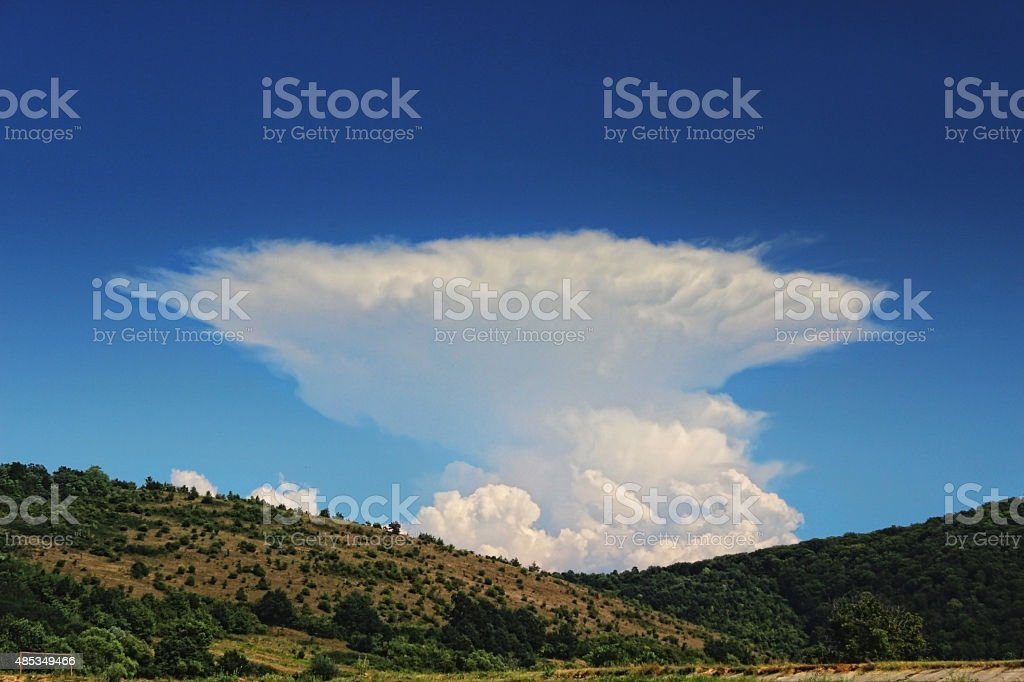 Anvil Storm Cloud and Blue Sky with Hills stock photo