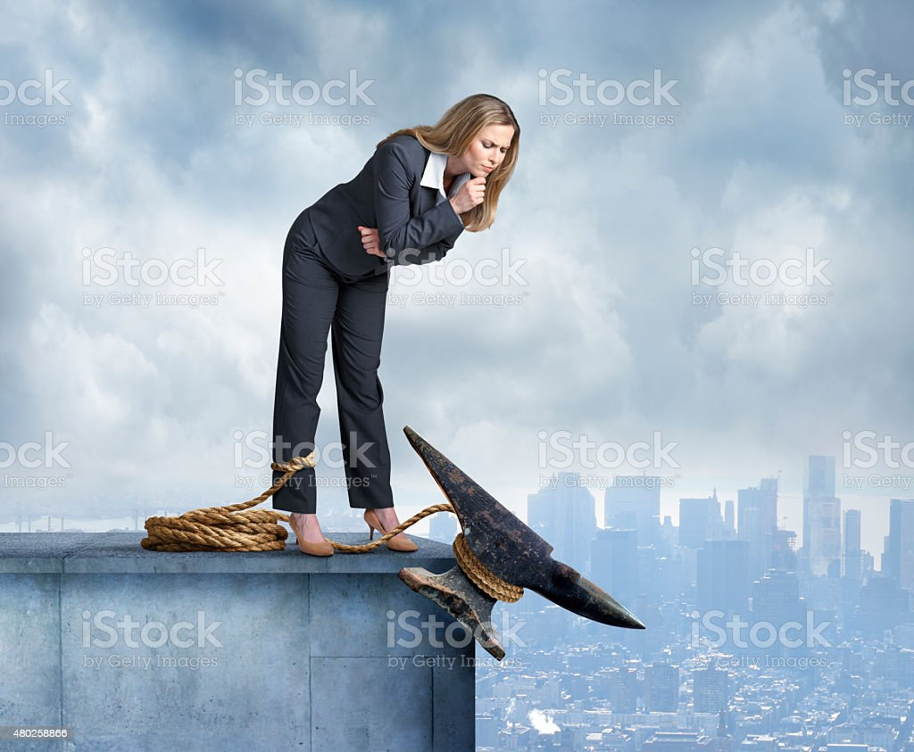 Anvil Tied Around Leg Of Businesswoman stock photo