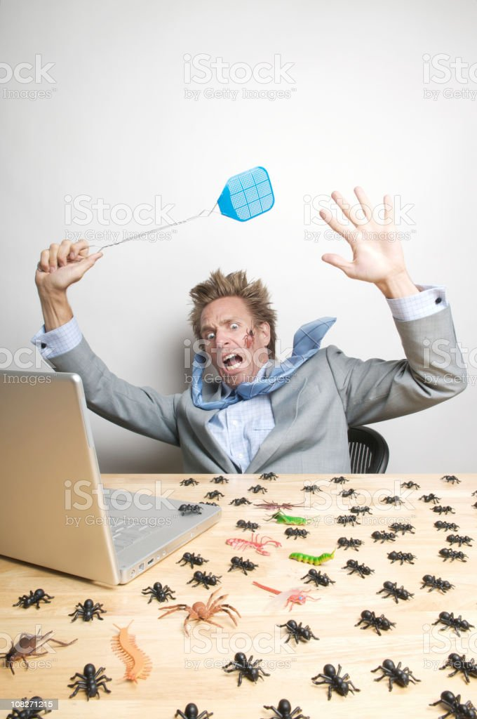 Anxious Businessman Fights Computer Bugs on Desk royalty-free stock photo