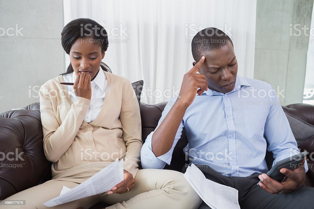 Anxious couple sitting on their couch royalty-free stock photo