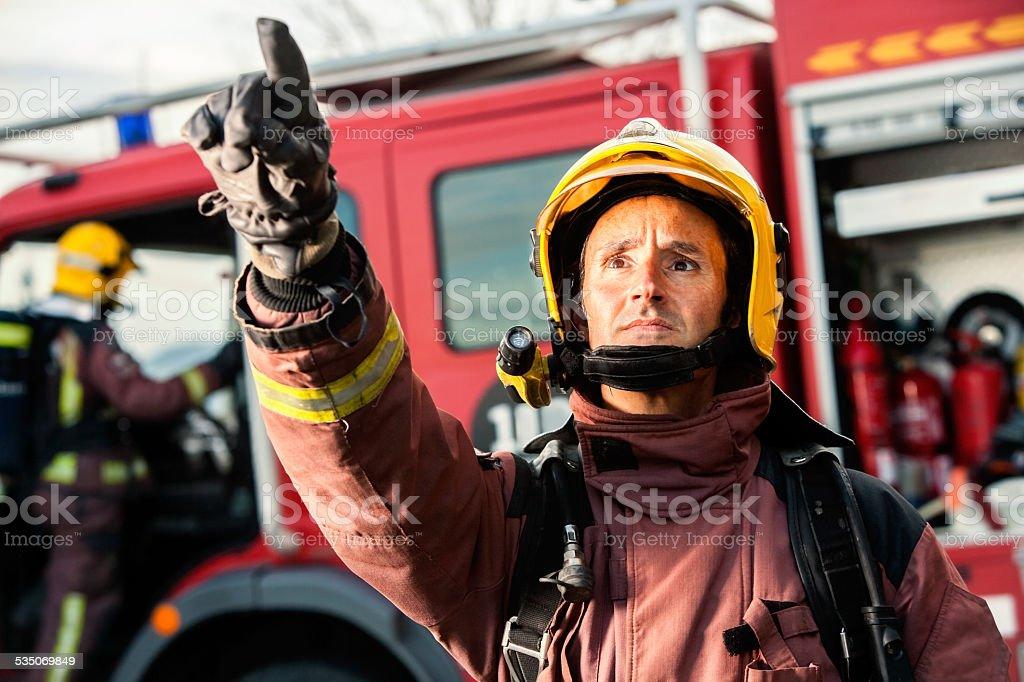 Inquiet fireman'pointant au feu. photo libre de droits