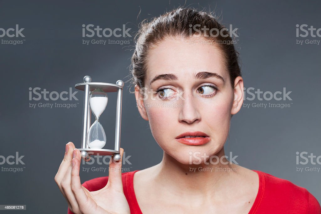 anxious girl with symbol of timing and deadlines in hands stock photo