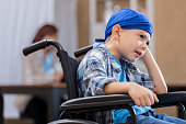 Anxious little boy in wheelchair in hospital waiting area