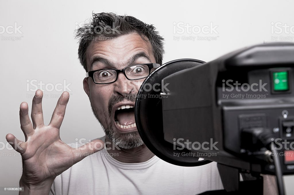 Anxious male photo model behind a strobe stock photo