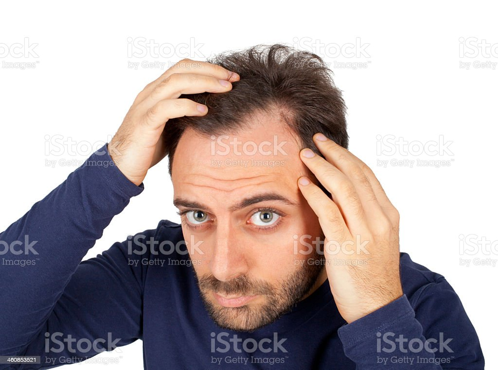 Anxious man inspecting hairline on white background stock photo