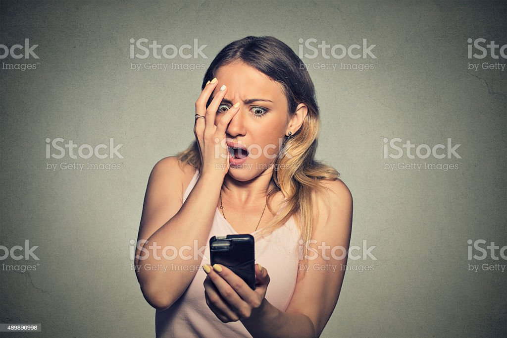 anxious scared girl looking at phone seeing bad news stock photo