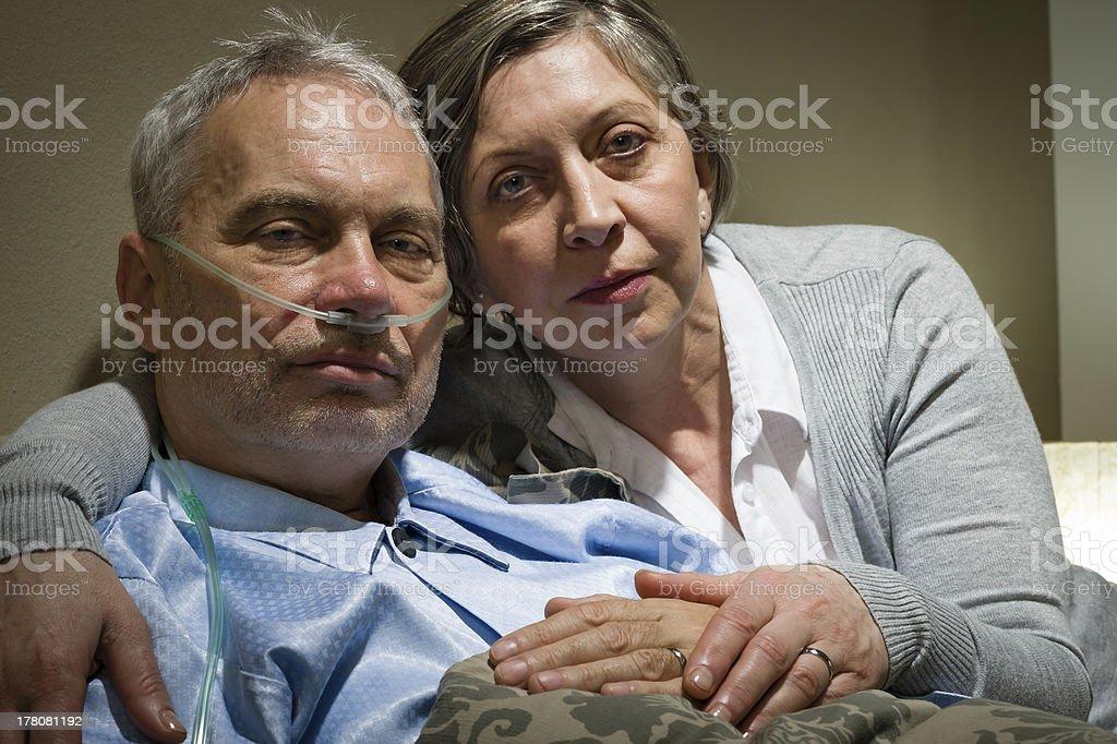 Anxious senior wife holding her sick husband stock photo