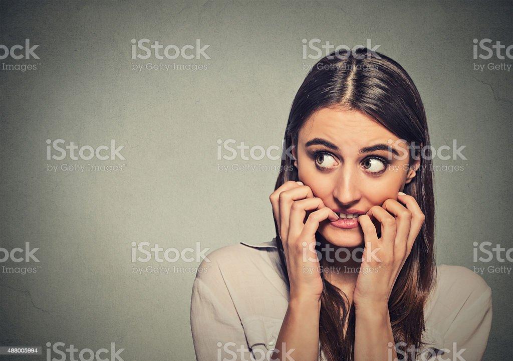 anxious unsure hesitant nervous woman biting her fingernails stock photo