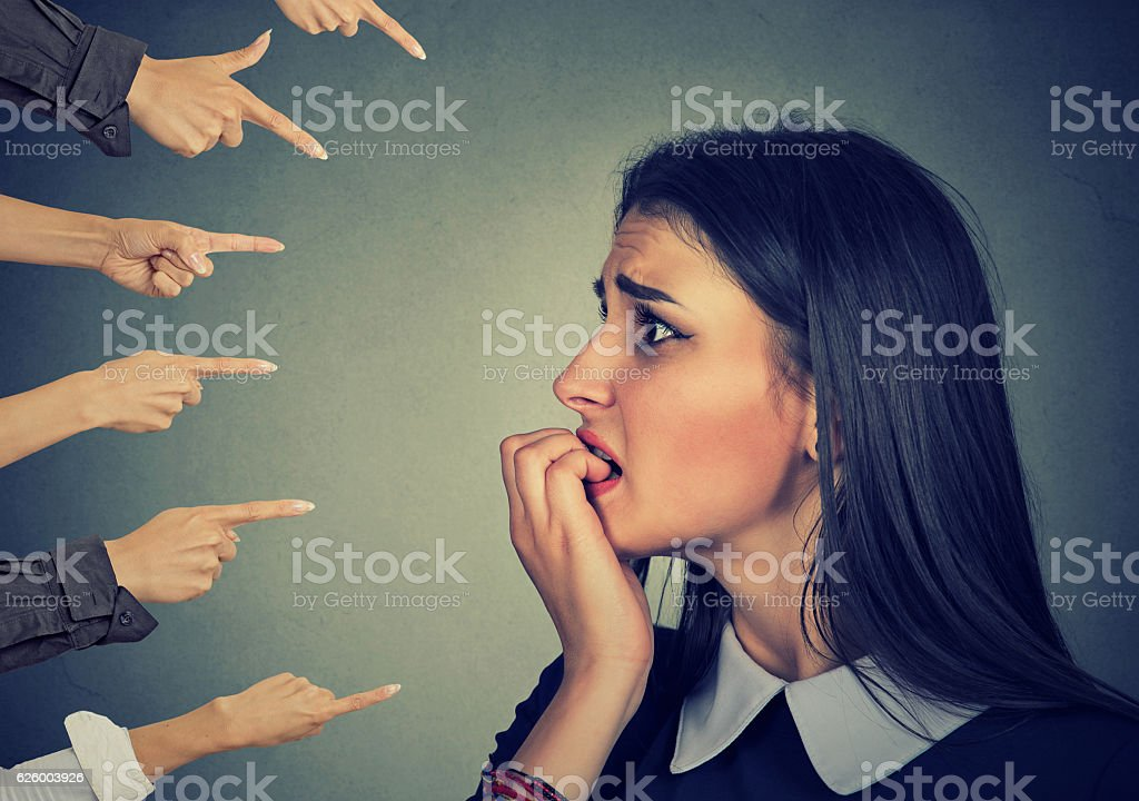 Anxious woman judged by different hands. Accusation concept stock photo